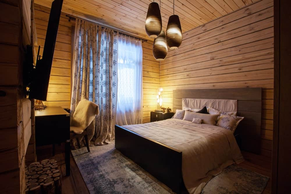Rustic master bedroom with a modish bed set on a large gray rug covering the hardwood flooring. The room is lighted by a set of attractive pendant lights.