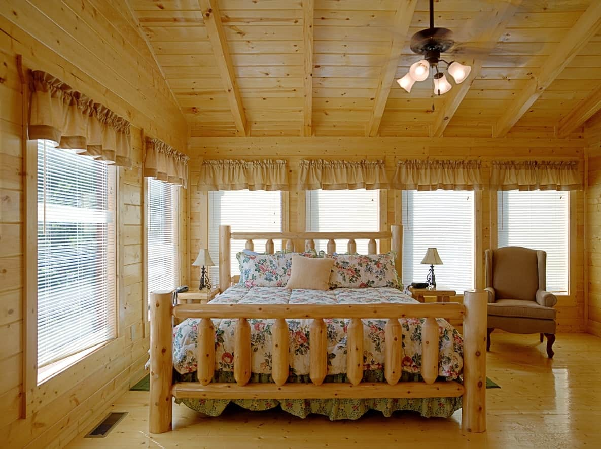 Medium-sized master bedroom featuring hardwood floors and multiple windows surrounding the room. The room offers a large bed lighted by two small table lamps on both sides.