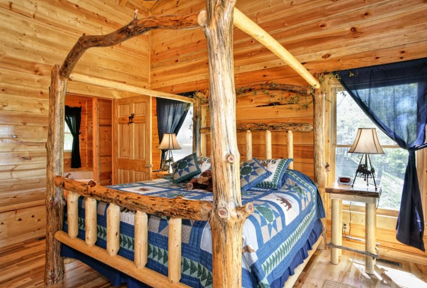 This master bedroom offers a rustic bed surrounded by wooden walls and ceiling, along with hardwood flooring.