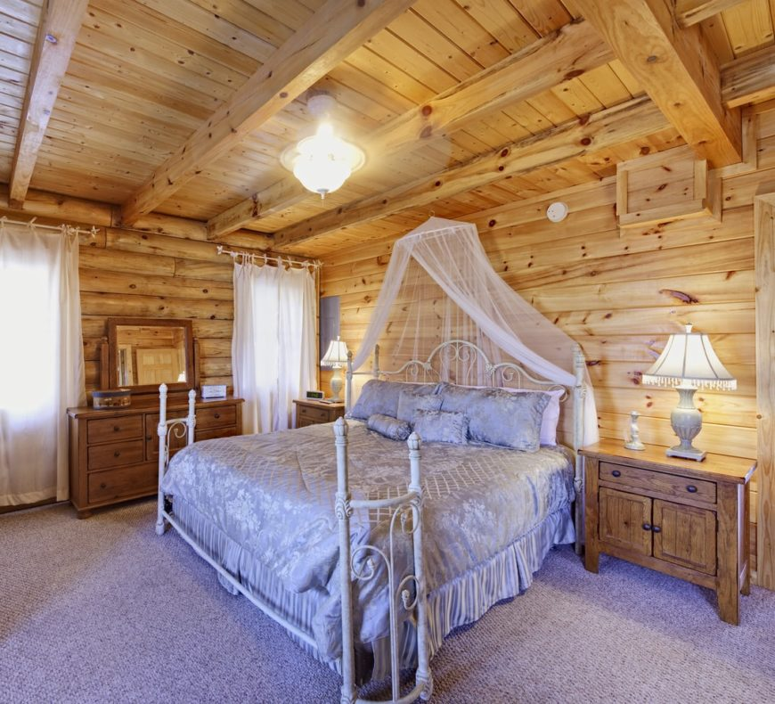 This master bedroom features rustic side tables and a classy bed set on the room's carpet flooring.