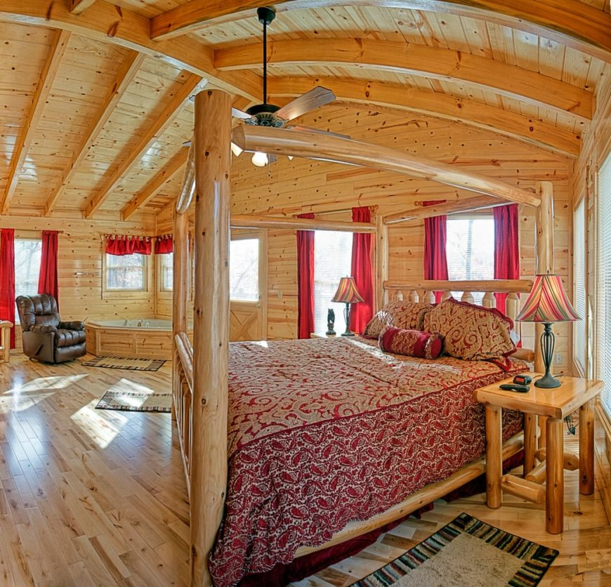 A master bedroom with a stunning ceiling with exposed beams. It also features a large bed set on the hardwood flooring. The room also offers a corner tub with a recliner chair on the side.