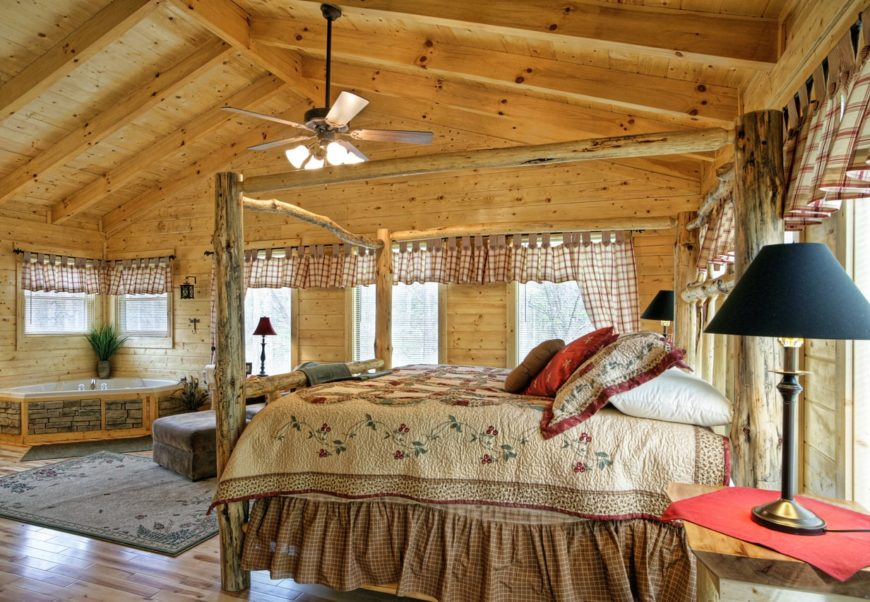 Large rustic master bedroom with hardwood flooring topped by a rug. The room also offers a corner tub.