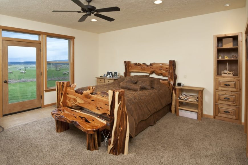 Master bedroom boasting a rustic and stylish bed set on the gray carpet flooring. The room has a doorway leading to the relaxing farm of the property.