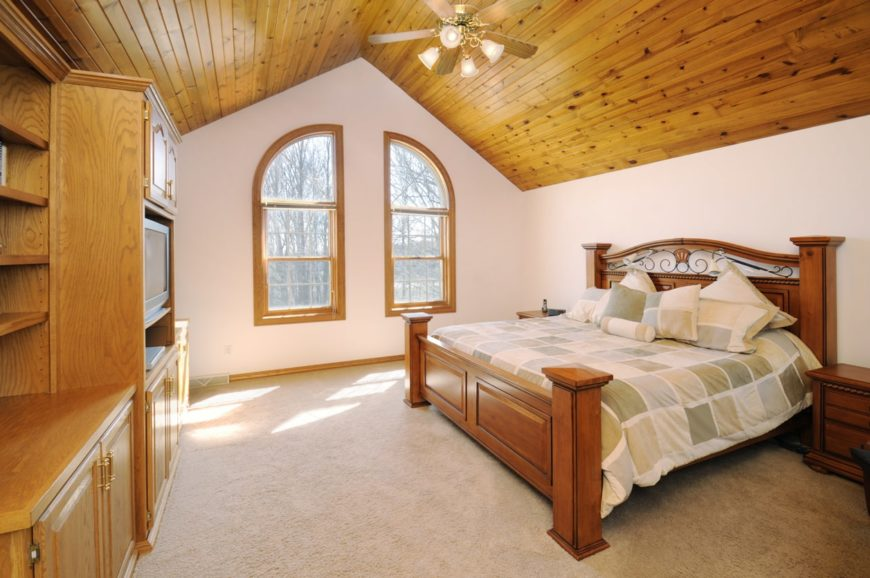 Master bedroom featuring a beautiful bed set on the carpet flooring. The room features a vaulted ceiling and white walls.