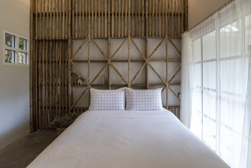 Master bedroom featuring a wall made of bamboo and a white bed near the glass windows covered by a lovely white curtain.