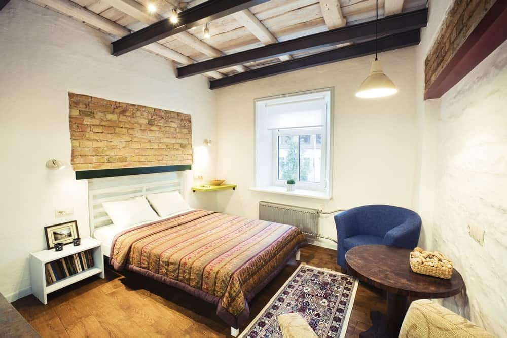 Small master bedroom featuring white walls and hardwood flooring, along with a bed and a blue chair. The wooden ceiling has black beams for additional style.