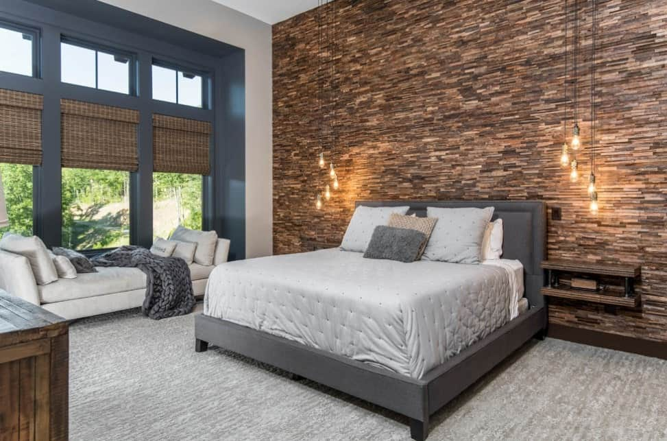 Large modern master bedroom with a mix of rustic style. The bed looks very stylish with its gray frame. There's a bench seating as well, near the windows.
