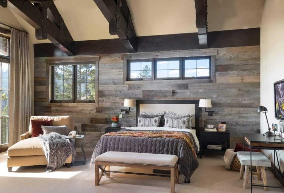 Master bedroom featuring a rustic wall and carpet flooring. There's a sitting area with a small coffee table and a study desk.