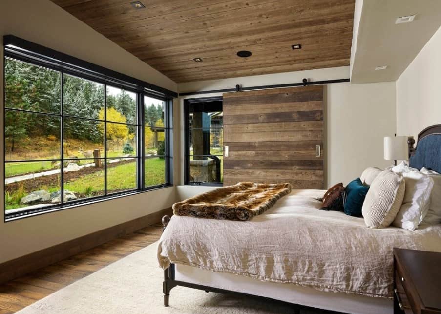 This master bedroom offers a large bed set on a large white rug covering the hardwood flooring. The room also features a rustic ceiling.
