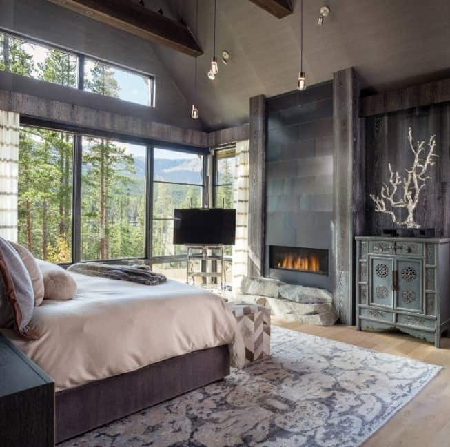 Master bedroom featuring hardwood flooring topped by a handsome rug and a fireplace. There are glass windows overlooking the relaxing surroundings.