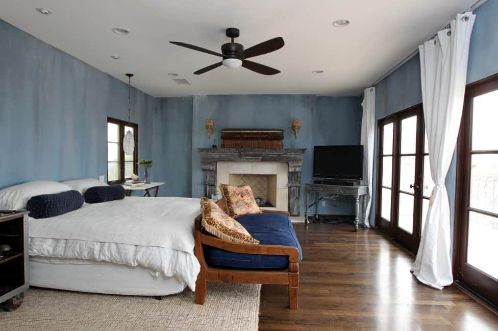 This master bedroom is surrounded by stylish blue walls and has hardwood flooring topped by a large rug. The room also offers a large white bed and a fireplace.