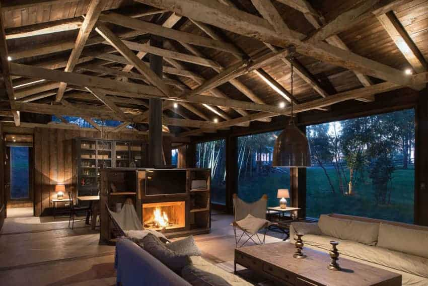 This Rustic-style living room is a part of a great room that also houses the dining area under its wooden cathedral ceiling with exposed wooden beams that support the thin metal chimney of the fireplace and a pendant light hanging over the wooden coffee table in between the couches.