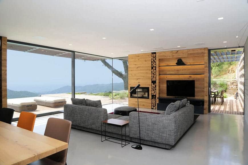 The gray L-shaped sectional sofa complements the light gray tiles of the flooring that makes the black entertainment cabinet stand out as well as the TV against the wooden wall. This is brightened by the wide glass walls with a view of the wooden deck outside.