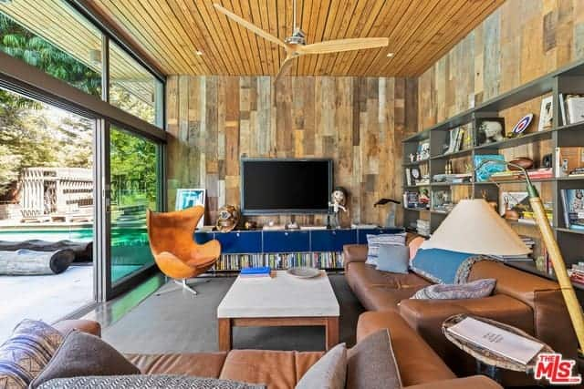 The two brown leather sofas works well with the wooden walls and wooden ceiling that has a plank shiplap finish. This is contrasted by the gray carpeted flooring that matches with the gray shelves behind the couch and illuminated by the sliding glass doors.
