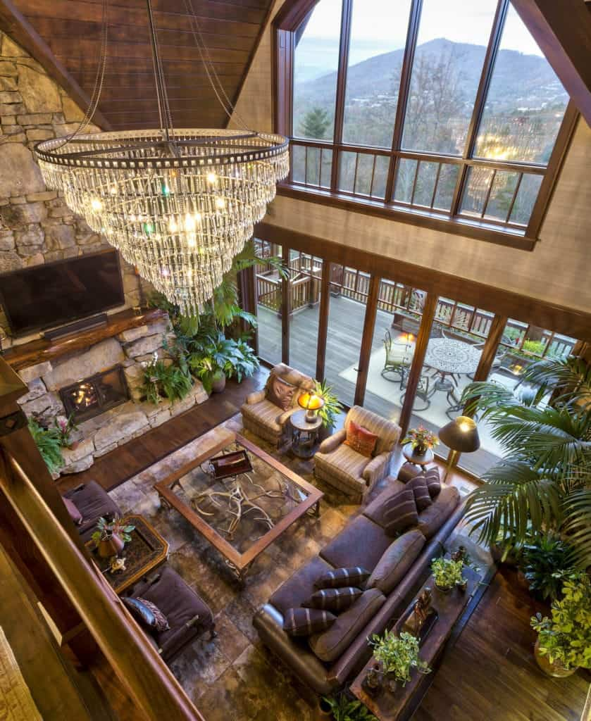 The highlight of this Rustic-style living room is the majestic crystal chandelier hanging over the glass-top coffee table with deer antlers for legs. This is surrounded by a chocolate brown sofa set and a couple of striped cushioned armchairs over a brown velvet area rug.