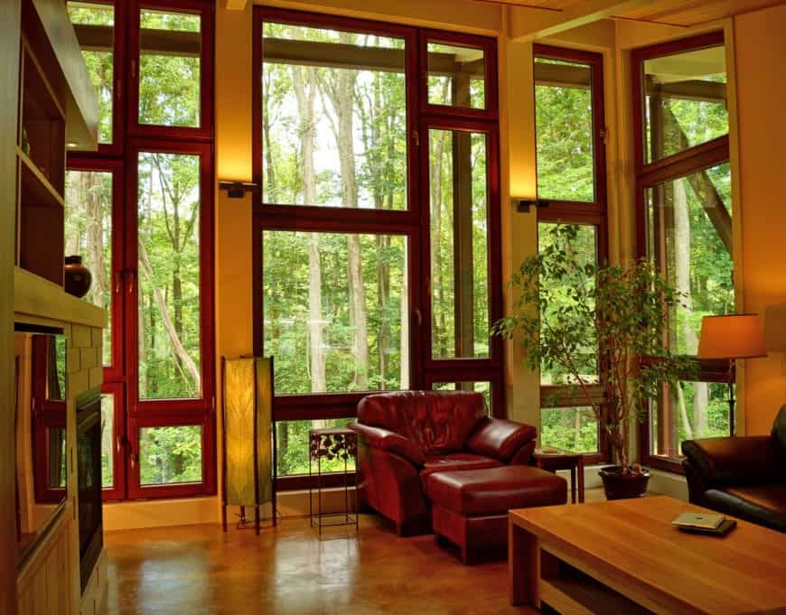 The view of the lush green forest outside the large glass wall sets a nice contrast to the redwood frames of the windows that matches with the leather cushioned armchair with its own matching leather foot stool.