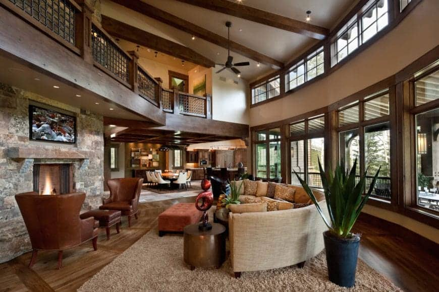 This Rustic-style living room is a part of a great room that also houses the dining area. Most of the space is given to the living room that has a high ceiling that has exposed wooden beams and a large curved wall filled with windows matching the curved sectional sofa.