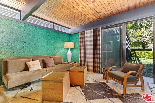 The brown velvet couch stands out against the wall that is dominated by a patterned green wallpaper. This wall is contrasted by the wooden ceiling with exposed gray beams. These are all illuminated by the natural lights coming in from the sliding glass doors.
