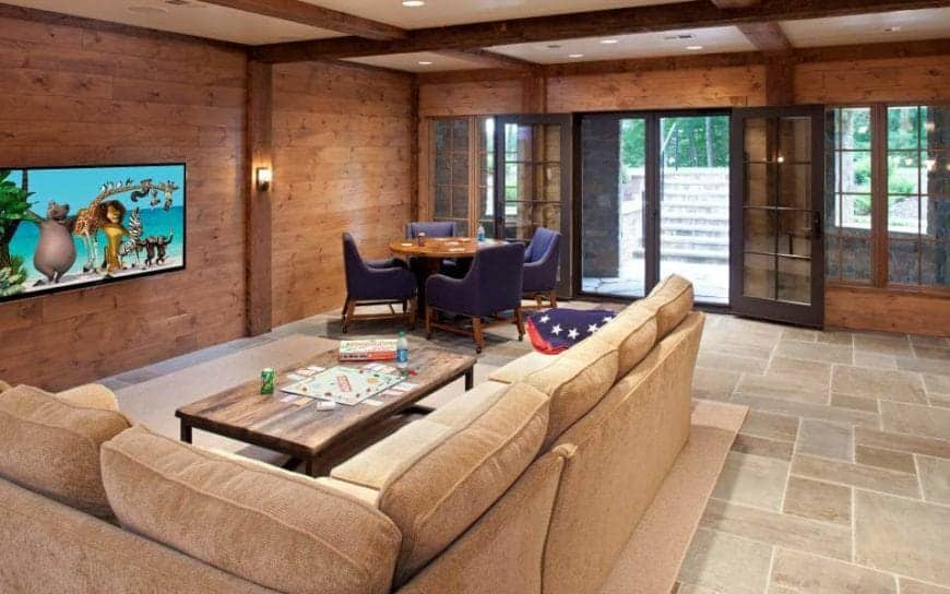 This living room has a beige ceiling with exposed wooden beams that blend with the wooden walls. One side houses the wall-mounted TV and adjacent to it is a wooden wall dominated by windows and a pair of glass doors that brighten up the beige marble flooring.
