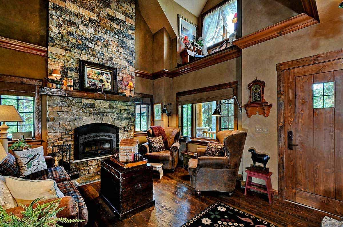 This small and cozy Rustic-style living room looks like it gives a warm hug to those who enter the main wooden door beside it. There is a fireplace embedded into a large stone column. This is paired with a checkered sofa and a couple of brown leather cushioned armchairs.