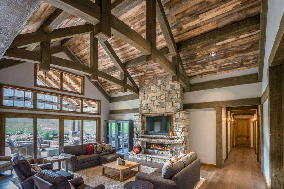 The modern fireplace is embedded into a large stone pillar that also houses the TV. This stone pillar reaches all the way up to the wooden cathedral ceiling with exposed wooden beams illuminated by large transom windows above the tall glass sliding doors.