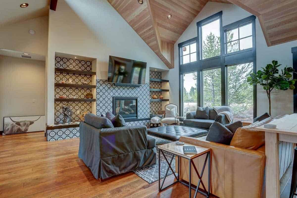 The high arched ceiling is paired with a tall floor-to-ceiling window on the right side that brings in an abundance of natural lights to the set of sofas, two of which has gray slipcovers. These are facing a complex patterned wall with built-in shelves housing the fireplace and TV.