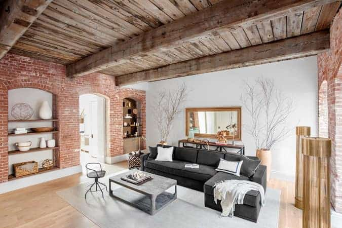 This Rustic-style living room has a beautiful red brick wall that has a couple of alcoves flanking the arched entryway into this room. This paired well with a wooden ceiling that has thick exposed wooden beams and adjacent wall of white that makes the dark gray sectional sofa stand out.
