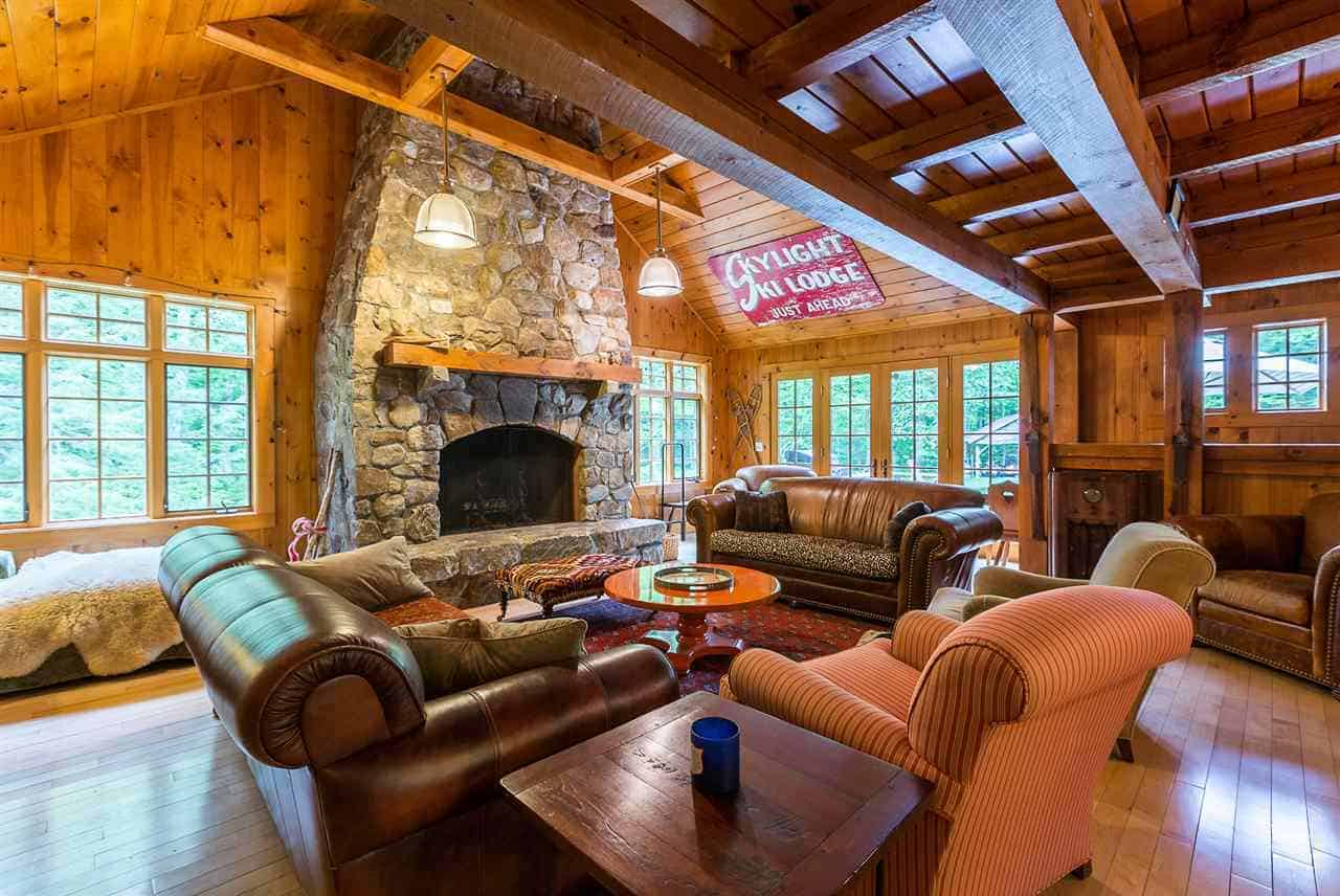 The wooden cathedral ceiling of this charming Rustic-style living room matches with the wooden walls that are filled with tall windows that feature the lush green landscape outside making the stone fireplace stand out as well as the brown leather sofas.