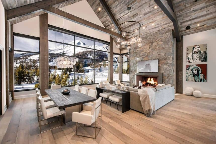 The large textured stone wall that houses the fireplace matches with the wooden hue of the cathedral ceiling with exposed wooden beams and a modern chandelier. This hangs over the L-shaped sofa brightened by the large glass wall with a snowy scenery outside.