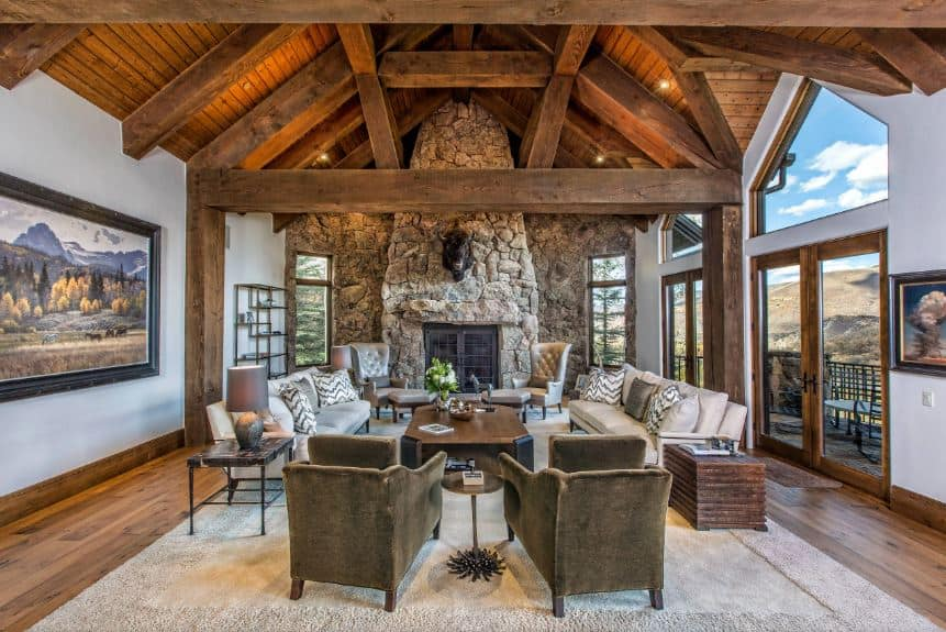 This wide and airy Rustic style living room is dominated by the large textured stone wall on the far end that has a mounted stuffed bison head over the fireplace. This matches well with the wooden cathedral ceiling that has large exposed wooden beams.
