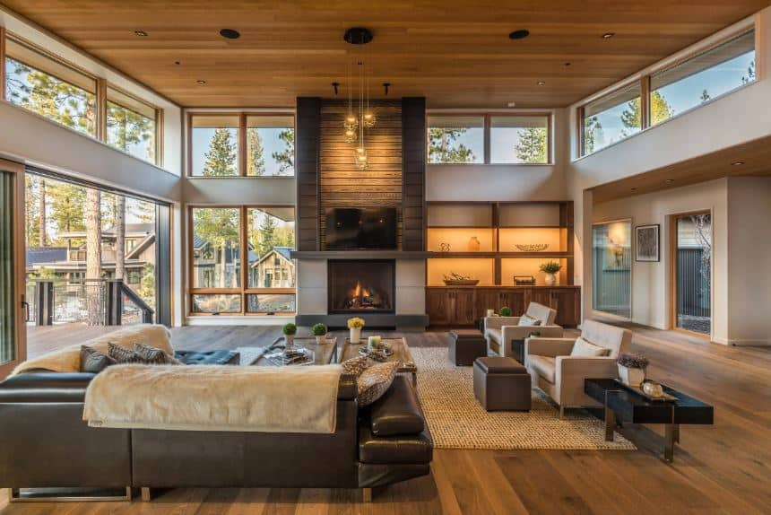 This is a spacious Rustic-style living room that is augmented by the bright natural lights coming in from the Glass walls, glass doors and transom windows that brighten up the hardwood flooring and the black leather L-shaped sectional sofa.