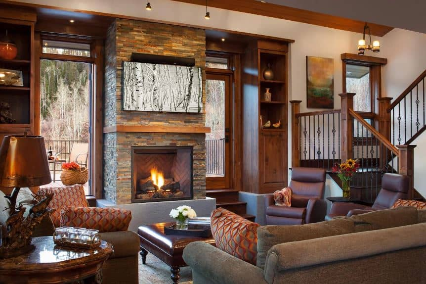The large stone pillar that houses the fireplace is flanked by a glass window on one side and a glass door on the other that leads to a balcony outside. The wooden frames of these matches with the wooden structures of the room as well as the cushioned coffee table in front of the gray sofa.