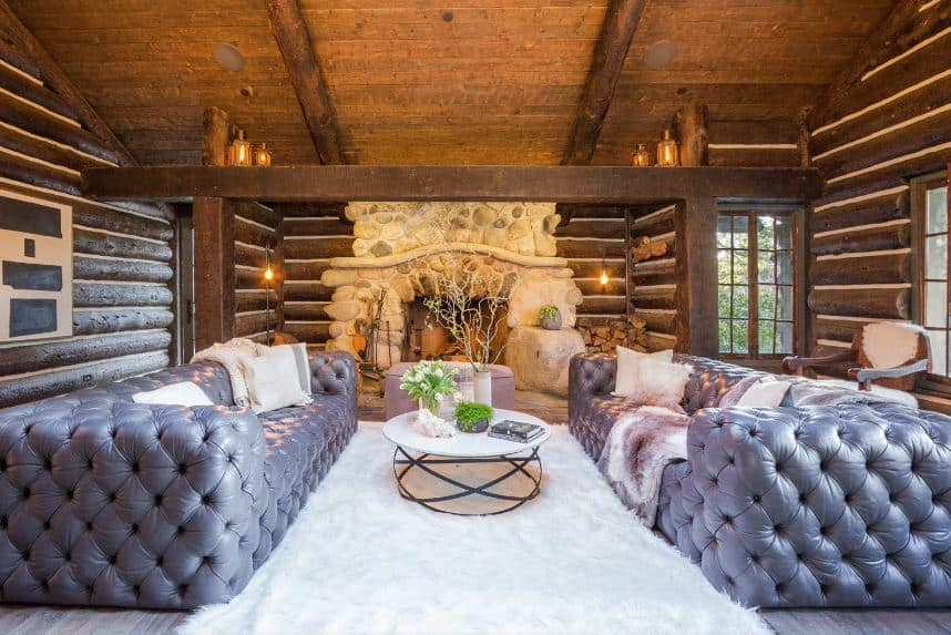 The highlight of this Rustic-style living room are the pair of gray tufted sofas flanking a white circular coffee table over the white furry area rug. This setup stands out against the wooden shed ceiling that has exposed wooden beams matching the log beams of the walls.
