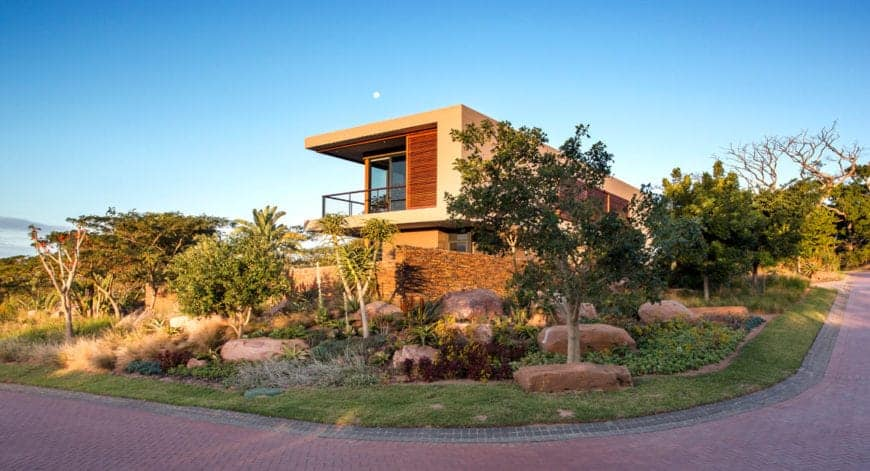 An abundant garden with tall trees flourishes in this two-story modern house and it adds privacy as well together with its bricked walls.