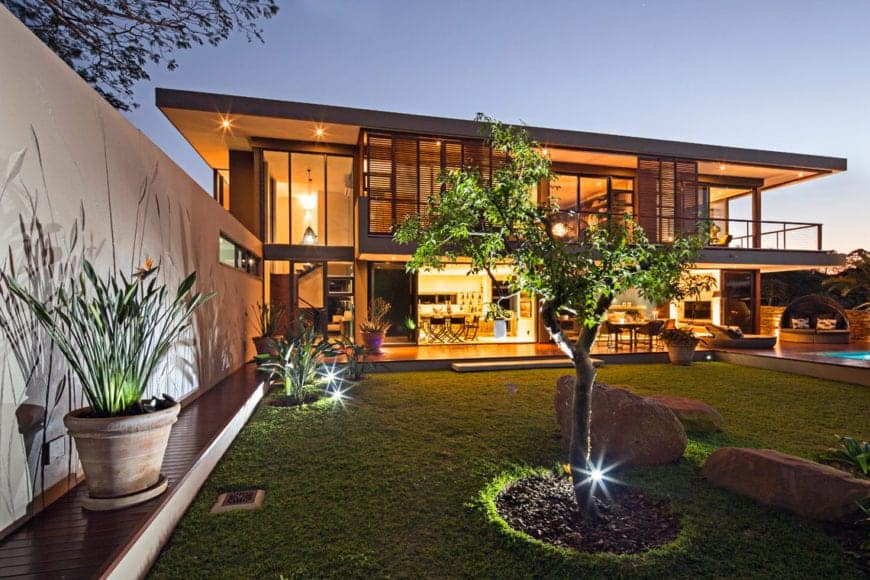 A bermuda grass carpets this big front yard with adequate plants and big rocks. Big potted plants and a beautiful tree with its own stony bed complement this contemporary house.