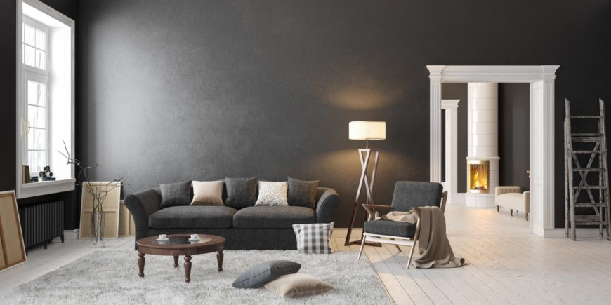 The spacious living room offers a black sofa and chair along with a gray shaggy rug topped with a wooden table and throw pillows.