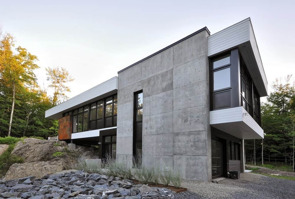 A modern, minimalist house on a rock with a double ground level one of which is covered by rocks. The uniqueness and sleekness of this house are undeniable.