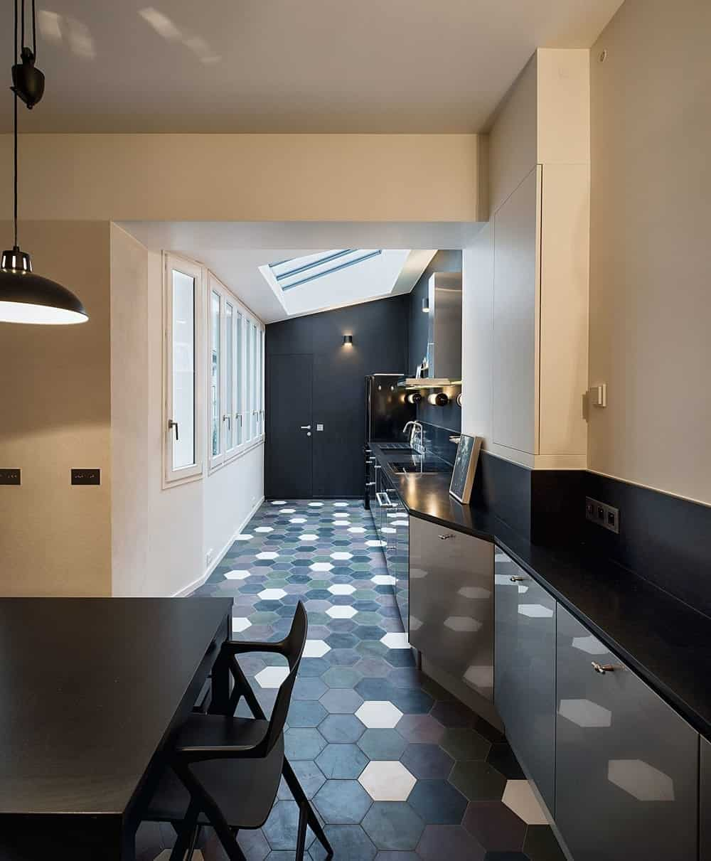A long kitchen accented with multi-colored hex floor tiles. It includes stainless steel cabinetry topped with black granite counter and vaulted ceiling with skylight bringing natural light in.