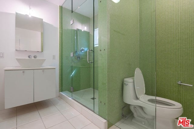 Contemporary master bathroom with green tiles walls fitted with glass enclosure. It includes a floating vanity with vessel sink and paired with a frameless mirror.