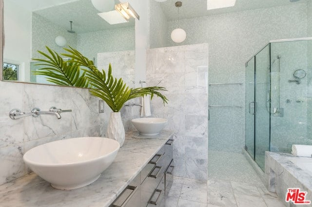 A marble primary bathroom features his and hers vessel sink vanity along with a walk-in shower area.