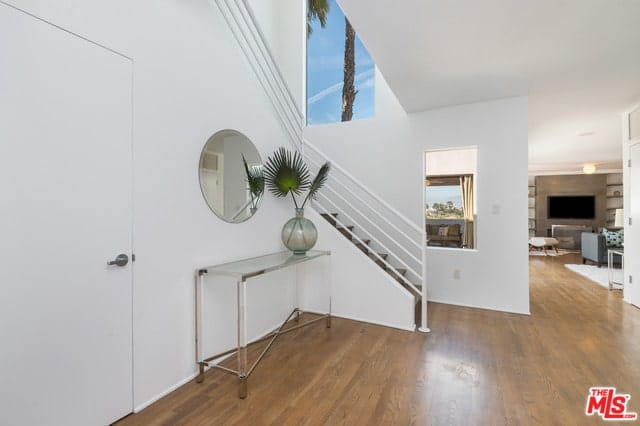 A round frameless mirror hung over a glass console table that's decorated with a glass vase in this foyer. It is positioned against the white staircase over hardwood flooring.
