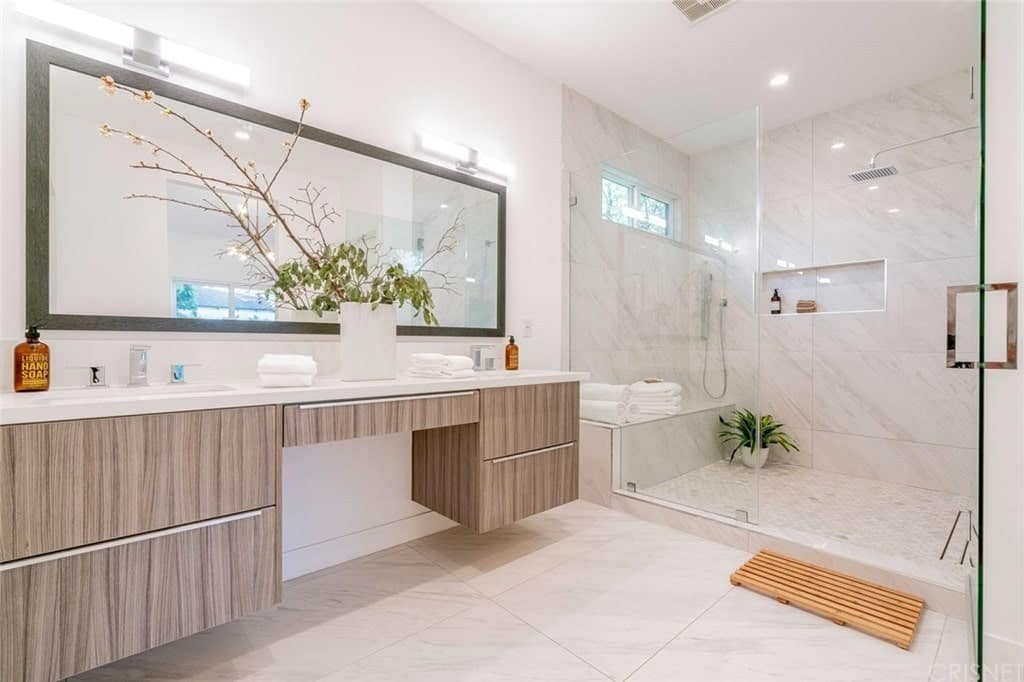 Fresh primary bathroom accented with potted plants features a walk-in shower and floating vanity lined with a rectangular mirror and lighted by wall lamps.