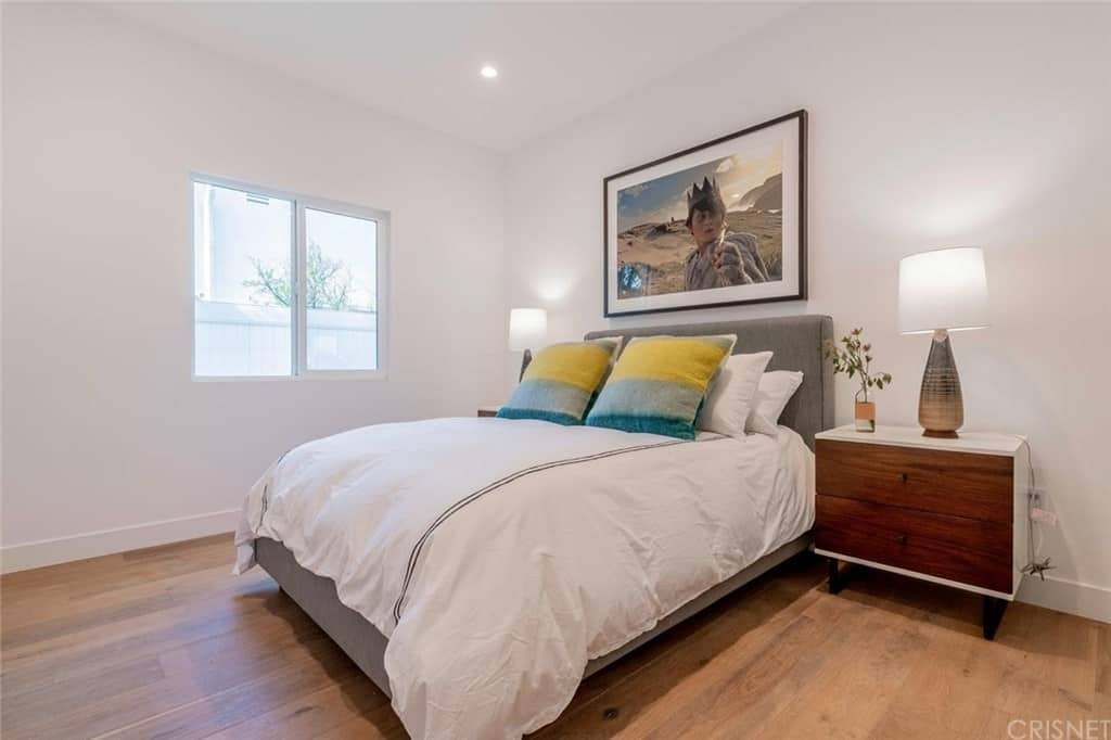 Simple master bedroom with gray bed and wooden nightstand over a hardwood flooring. It is accented with multi-colored throw pillows and a wall art mounted on the white wall.