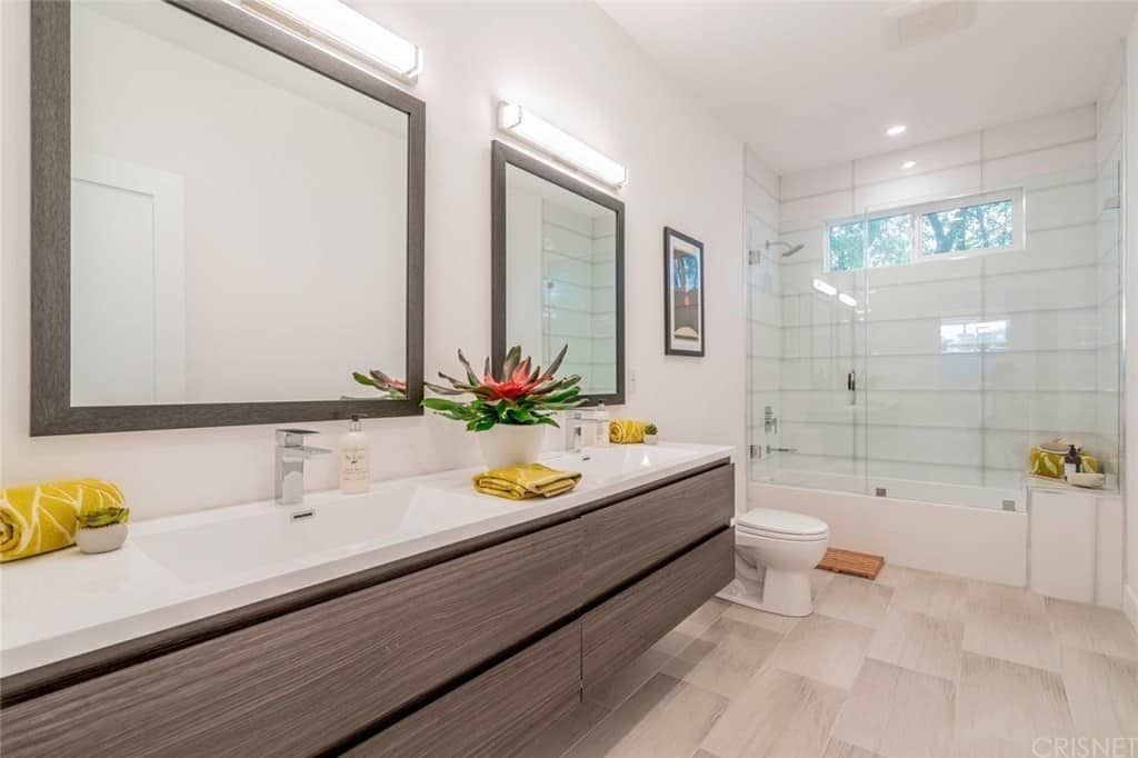This bathroom boasts a huge dual vanity sink paired with wooden mirrors and lighted by rectangular wall lamps. It has a toilet and walk-in shower area.
