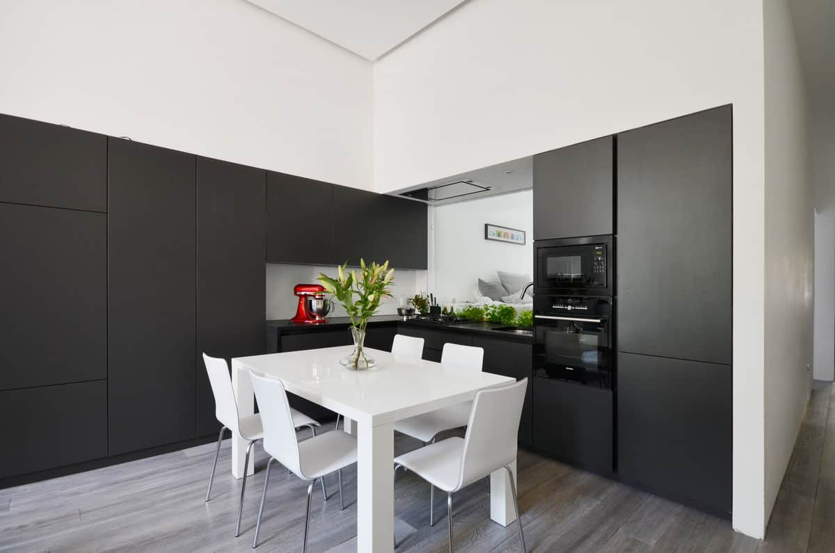A two-toned kitchen features sleek black cabinetry and white breakfast table surrounded with white chairs over hardwood flooring.