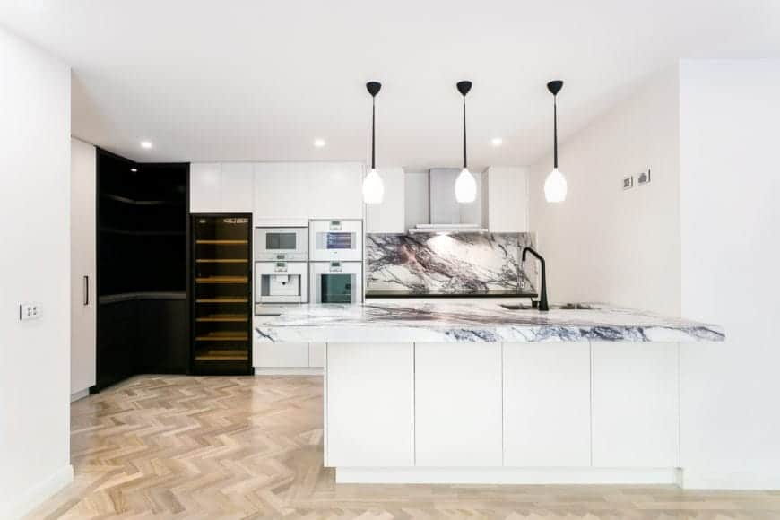Gorgeous white kitchen accented with black shelves and granite countertops that matches the backsplash along with a hardwood flooring that has a herringbone pattern design.