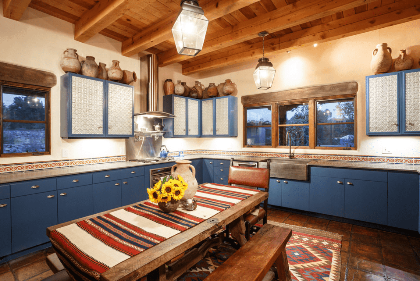 Southwestern kitchen features blue cabinetry and slate flooring. The room is decorated with rustic pottery vases and pendant lights.