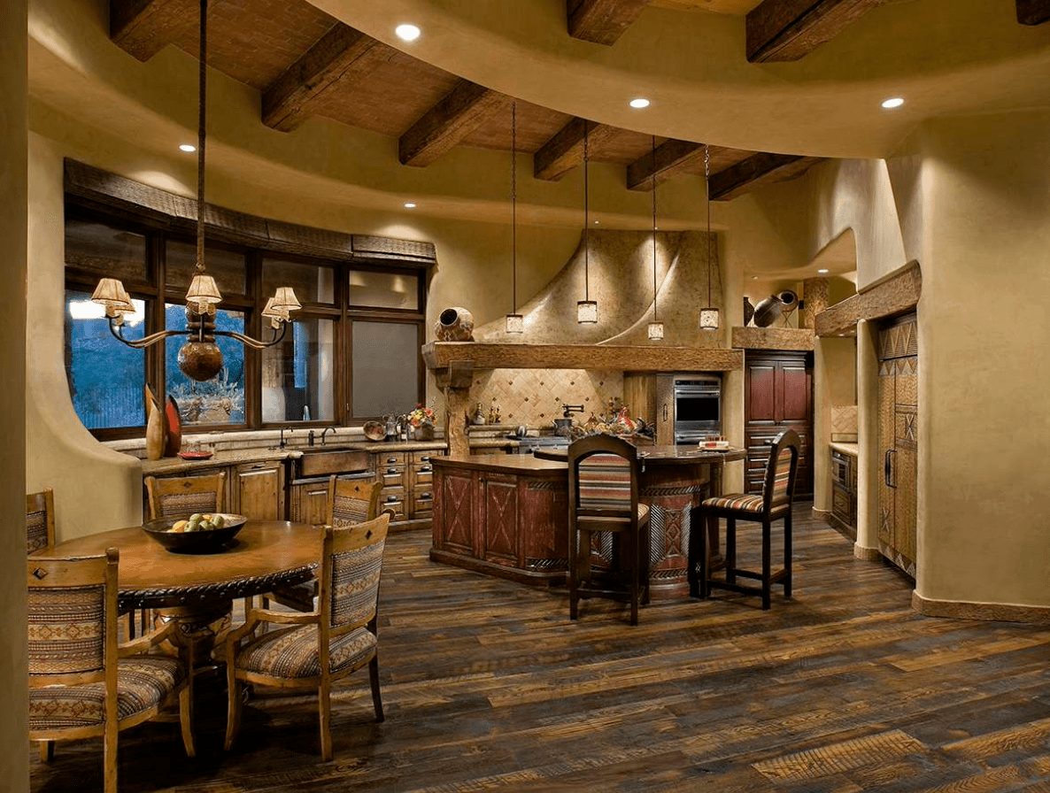 Warm kitchen accented with wood beams and hardwood flooring. It has a breakfast island and dining space illuminated by pendant lights and chandelier.