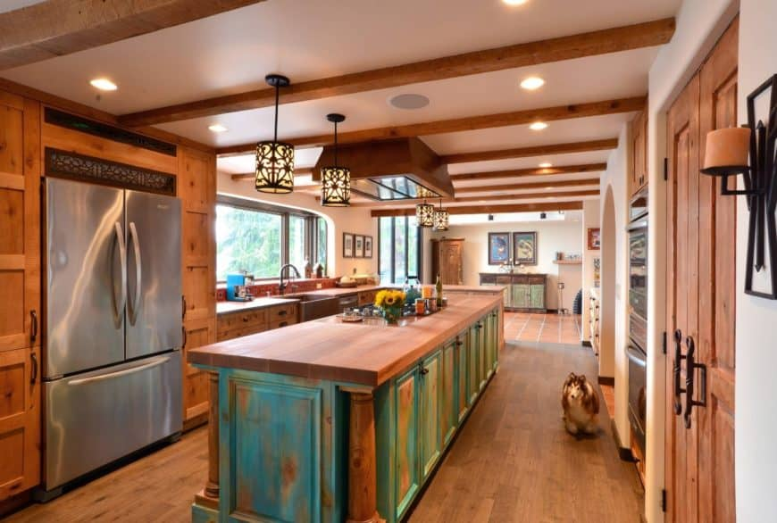 Green distressed breakfast island with wide plank wood top adds a rustic tone in this kitchen. It has fancy pendant lights along with the wooden cabinetry and hardwood flooring.