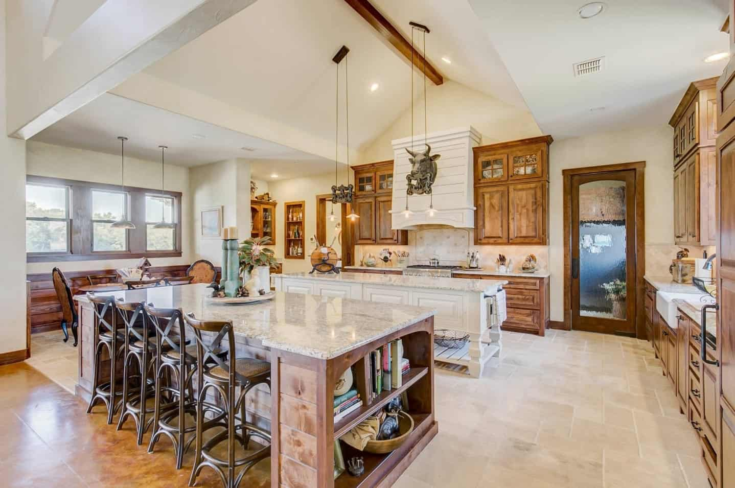 Luxurious kitchen boasts a double breakfast island and a shiplap vent hood mounted with a bull head decor.